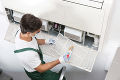 Young male technician cleaning. Air conditioner indoors Royalty Free Stock Photos