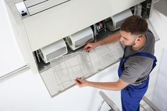 Young male technician cleaning. Air conditioner indoors Royalty Free Stock Images