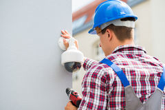Young Male Technician Installing Camera On Wall. Using Electric Cordless Drill Stock Photo