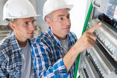 Young male technician learning to examine fusebox with multimeter probe royalty free stock photography