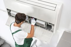 Young male technician repairing air conditioner. Indoors Royalty Free Stock Photography