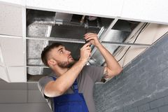 Young male technician repairing air conditioner. Indoors Stock Image