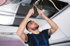 Young male technician repairing air conditioner. Indoors Stock Photo