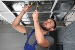 Young male technician repairing air conditioner. Indoors Stock Photography