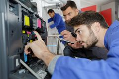 Young male technician repairing digital photocopier machine. Male Royalty Free Stock Photos