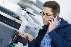 Young male technician repairing digital photocopier machine. Phone Royalty Free Stock Photography