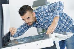 Young male technician repairing digital photocopier machine. Printer Royalty Free Stock Image