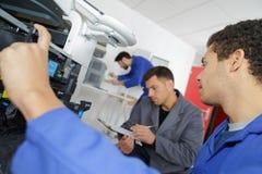 Young male technician repairing digital photocopier machine. Fixing Stock Photos