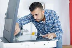 Young male technician repairing digital photocopier machine. Man Stock Photos