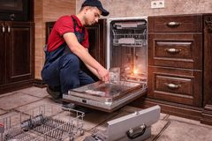 Young Male Technician Repairing Dishwasher In Kitchen stock image