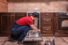 Young Male Technician Repairing Dishwasher In Kitchen stock photography