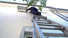 Young male technician repairing outdoor air conditioning system. Standing on aluminum ladder stock photos