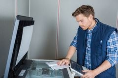 Young male technician repairing printer at office. Young male technician is repairing a printer at office Stock Image