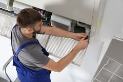 Young male technician repairing. Air conditioner indoors Royalty Free Stock Photo
