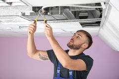 Young male technician. Repairing air conditioner indoors Royalty Free Stock Photo