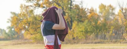 Young male teenage hipster put on a sweatshirt sweater outdoors walking in nature field f stock images