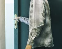 Young male teenager in checkered shirt leaving home and closes door stock images