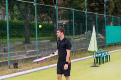 Young male tennis player wearing a sportswear warming up before. Tennis match on a court outdoor in summer or spring Stock Photos