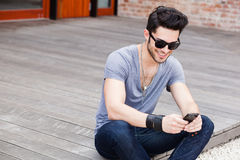 Young male texting on a smartphone. Attractive young male model playing games on a smart-phone Royalty Free Stock Photo