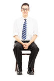 Young male with tie sitting on a wooden chair waiting for job in. Terview isolated on white background Royalty Free Stock Photo