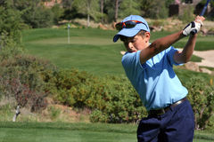 Young male about to tee off. Young male with blue shirt about to hit a ball on a beautiful golf course with flag visible, focus on golfer Stock Photos