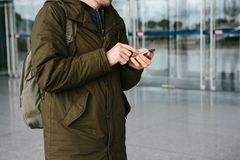 A young male tourist at the airport or near a shopping center or station calls a taxi or talks on a cell phone or. Communicates with friends using a mobile Stock Photo