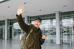 A young male tourist at the airport or near a shopping center or station calls a taxi or talks on a cell phone or. Communicates with friends using a mobile Royalty Free Stock Photography