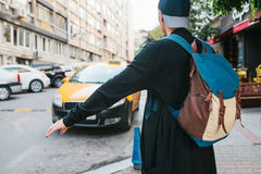 Young male tourist with a backpack in the big city is waiting for a taxi. Journey. Sightseeing. Travel. Young male tourist with a backpack in the big city is Stock Image