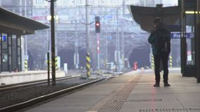 Young male tourist with backpack waiting on train at the platform, traveling. Stock footage stock footage