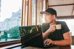 A young male tourist blogger freelancer working on a laptop in a cafe in Istanbul. A view from the window to the world Royalty Free Stock Photos