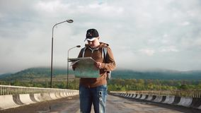 Young male tourist checking his way on route with map when walking on empty highway in mountains.  stock footage