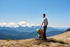 Male hiker with backpack in the mountains. Young male tourist enjoying morning sun on top of the mountain after a hike copyspace relaxation recreation travelling Royalty Free Stock Image