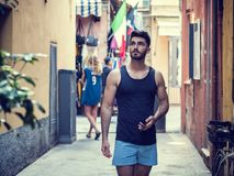 Young male tourist exploring old italian town. Of Alassio in Liguria region, with characteristic narrow alley and bright colors Stock Image