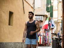 Young male tourist exploring old italian town. Of Alassio in Liguria region, with characteristic narrow alley and bright colors Royalty Free Stock Photo