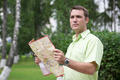 Young male tourist lost and looking around. Young male tourist with map in hand looking around. Tourist map of the city of Moscow, Russia (no trademark Royalty Free Stock Photos