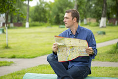 Young male tourist lost and looking around. Young male tourist with map in hand looking around. Tourist map of the city of Moscow, Russia (no trademark Royalty Free Stock Photo