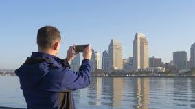 Man use phone taking street photo. Urban life. stock video