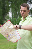 Young male tourist with map in hand looking at wristwatch. Tourist map of the city of Moscow, Russia (no trademark Stock Photo