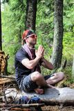 A young male tourist is meditating in the mountains royalty free stock photography