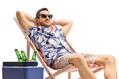 Young male tourist relaxing in a deck chair next to a cooling box with bottles of beer. Isolated on white background stock photos