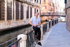 Young male tourist sitting on banister in Venice, Italy. Concept of last minute tours to Europe and romantic venetsian street Stock Photos
