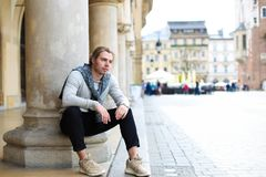 Young male tourist sitting near columns on Main Square in Krakow, Poland. Young male tourist wearing casual clothes and sitting near columns on Main Square in Stock Photo