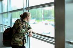 Young male tourist standing with backpack at airport waiting room, wearing camouflage shirt. Young male tourist standing near window with backpack at airport Stock Photography