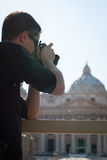 Young male tourist taking photos. Handsome young male tourist taking photos at St. Peter's Square in Vatican (St. Peter's Basilica in the background Royalty Free Stock Photo