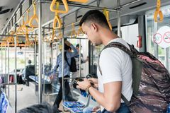 Young male tourist using the mobile phone. Young male tourist with a big backpack using the mobile phone for guidance or communication while standing in the bus Royalty Free Stock Images