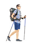 Young male tourist walking with hiking poles. Full length portrait of young male tourist walking with hiking poles isolated on white background Royalty Free Stock Photography