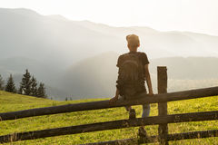 Young male tourist wih backpack sits on fence in hill side enjoying beautiful sight of mountains. Hiker takes rest and looks at distant ukrainian carpathian Stock Images