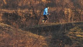 Runner athlete training. Young male trai runner training outdoors in autumn time alone stock video footage
