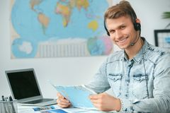 Young male travel agent consultant in tour agency holding map Stock Photos
