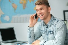 Young male travel agent consultant in tour agency phone call. Young man travel agent in tour agency sitting phone conversation smiling excited Stock Photos